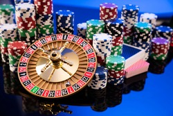 Casino and gambling concept. Roulette wheel, poker chips, dice. Blue background.