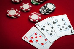 Casino card gambling and poker hand concept with a three of a kind (trip sevens) being paid out with red, green and black gaming chips on a red felt