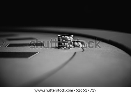 Casino chips are colorful game objects that lie on the gaming table in the stack / vintage photo processing / black and white photography. Background for gambling / casino, business, poker