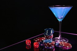Casino chips, dice and cocktail on dark background, space for text