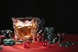 Casino chips, dice and glass of whiskey on red table against black background, space for text