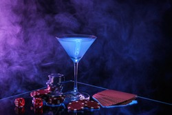 Casino chips, dice, playing cards and cocktail on dark background with smoke, space for text