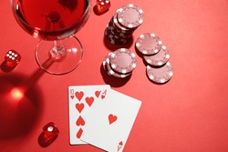 Casino chips, playing cards, dice and cocktail on red  table, flat lay