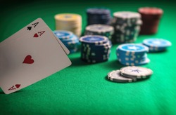 Casino, gambling concept. Two aces and poker chips on green felt background