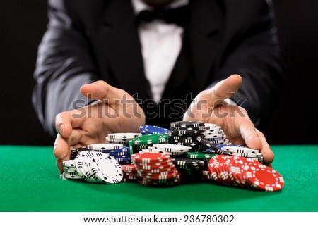 casino, gambling, poker, people and entertainment concept - close up of poker player with chips at green casino table ストックフォト ©