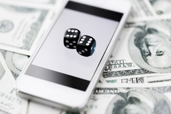 casino, online gambling, technology and fortune concept - close up of black dice, smart phone and dollar cash money