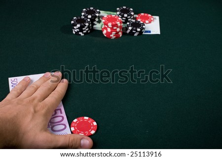 Casino player concept. pile of gambling chips and money on table. Focus on hand