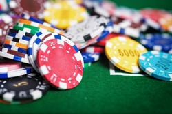 Casino poker chips on the green table.