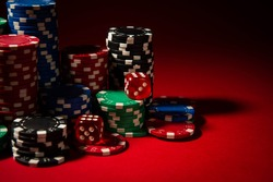 Casino. Poker. Game chips and dice lie on the table against a red background. Game chips for betting in gambling. Dice. Poker chips.