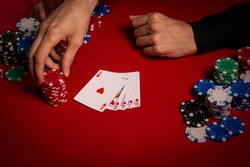 Casino. Poker. Hands of a gambler. Poker player. Game chips and dice lie on the table against a red background. Game chips for betting in gambling. Dice. Poker chips.