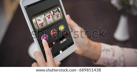 Casino slot machine game on mobile screen against close-up of woman hands using digital tablet