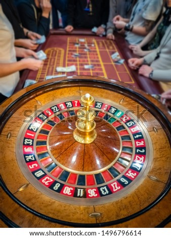Casino. Table with roulette. Game of roulette. Players make bets. Excitement. Cash game. Lose money. Win. Risky entertainment. The possibility of losing everything.