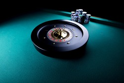 casino theme, high contrast image of casino roulette and playing chips on green canvas