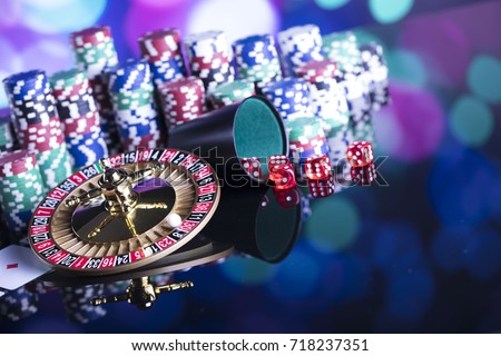 Casino theme. High contrast image of casino roulette, poker game, dice game, poker chips on a gaming table, all on colorful bokeh background.  #718237351
