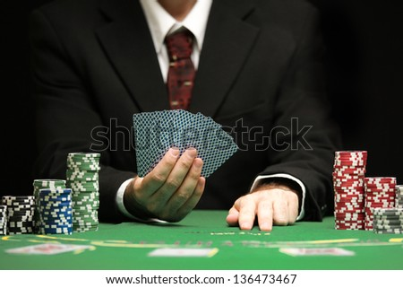casino worker holds cards