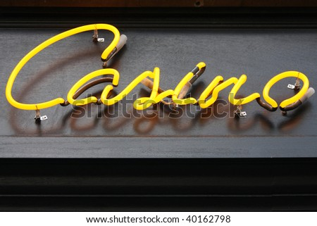 Casino - yellow illuminated neon sign. Outdoor advertisement.