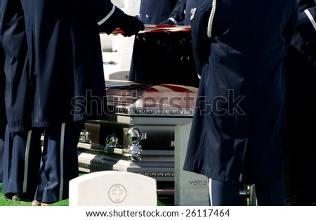 Casket at military funeral at Arlington National Cemetery with American flag reflected on casket
