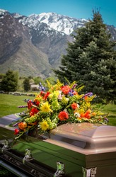 casket with flowers and mountain background