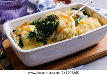 Casserole with cauliflower and spinach on a wooden background. Selective focus. #361904255