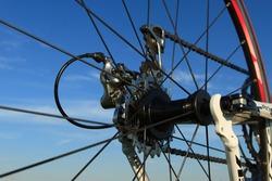 Cassette, derailleur and rear wheel of a modern racing bike with a blue sky. Shallow DOF.