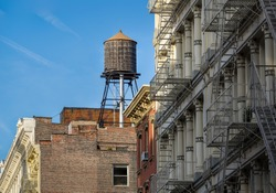 Cast iron facades of Soho loft buildings and rooftop wooden water tank, in Downtown Manhattan, New York City