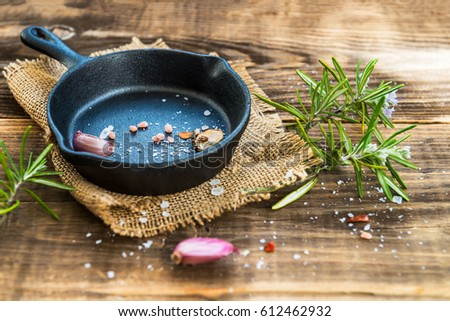 Cast-iron Frying Pan with  Spices on Rustic Wooden Background