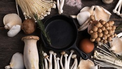 Cast Iron in the Center of Various Raw Mushroom Types - Portobello Mushrooms, Champignons, Shimeji, Enoki  Mushrooms. Mushrooms Background, Rustic Mood Top View