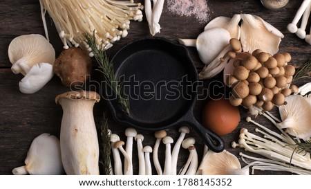 Cast Iron in the Center of Various Raw Mushroom Types - Portobello Mushrooms, Champignons, Shimeji, Enoki  Mushrooms. Mushrooms Background, Rustic Mood Top View