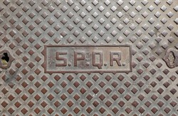 cast iron manhole cover with the inscription SPQR Which means Senate and People of Rome
