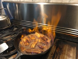 Cast iron skillet with sliced bananas. Cooked with sugar, butter, vanilla, cinnamon, brandy. Flambe,