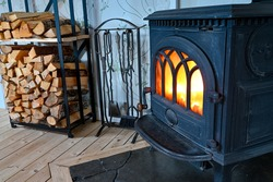 cast iron stove with fire and stacked wood beside