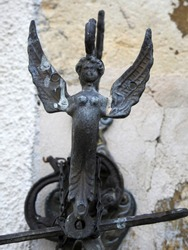 Cast iron winged angel figure atop a bell set against blurred cracked old wall background in southern France