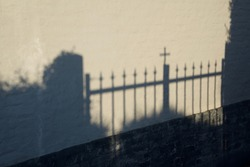 Cast shadow: the shadow of a closed entrance gate to a church is cast against a wall opposite by the evening sun