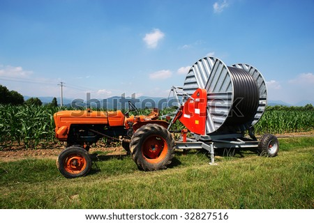 Castegnato (Bs),Franciacorta,a tractor with artificial irrigation in a corn field in June