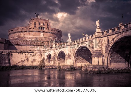 Castel Sant'Angelo (castle of Holy Angel) and Ponte or bridge Sant'Angelo with statues in Rome, Italy. Dramatic view of Sant'Angelo on Tiber River in storm. The vintage toned photo of Rome landmark. #585978338