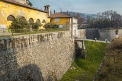Castello di Brescia. The entrance of the medieval fortress. The castle has watchtowers, a trench, a bridge made of white marble stones, bricks, in an Italian city Brescia, Lombardy, Italy