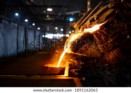 Casting, melting, molding and foundry. Bucket with hot molten iron pouring into the mold. Industrial steel production. Foto stock ©