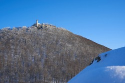 Castle also Stronghold (Teck) in winter on a clear evening with blue sky, many trees on the hill, big rock with snow in the foreground. Germany, Owen, Swabian alb.