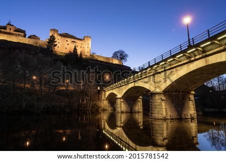 Castle and bridge illuminated at night of the medieval village of Puebla de Sanabria reflected on the Tera river, Zamora, Castilla y Leon, Spain Stock fotó ©