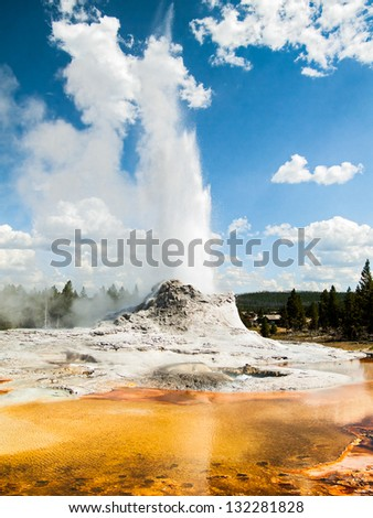 Castle Geyser, in Yellowstone National Park's Upper Geyser Basin, erupts with a colorful thermal pool in the foreground.