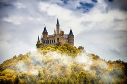 Castle on a wooded mountain in the fog under clouds, Hohenzollern, Germany
