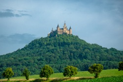 Castle on hill with towers surrounded by trees horizontal view
