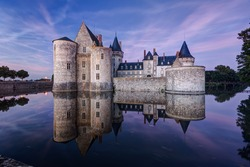 Castle or chateau de Sully-sur-Loire at night, France. This old castle located in the Loire Valley is a prime example of medieval fortress. Dramatic view of the strong castle on the water at dusk.