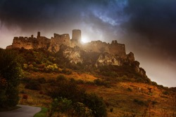 Castle ruins at top of hill in front of glowing sun and stormy sky