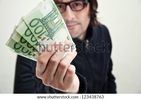 Casual adult man is paying in euros, corruption and bribe concept.