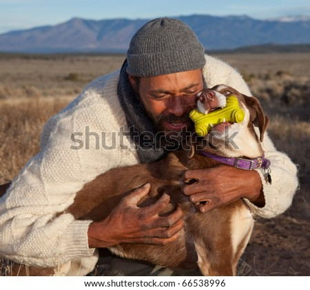Casual African American man hugging and playing with his dog.