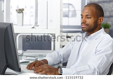 Casual afro businessman sitting at office desk, working on desktop computer.