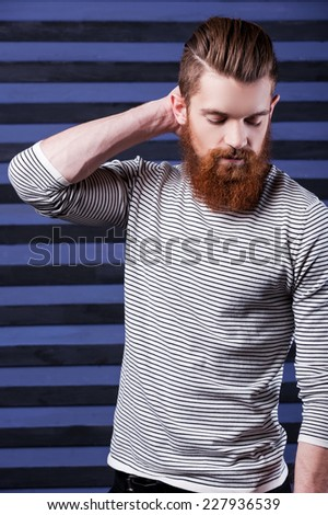 Casual and cool. Side view of handsome young bearded man holding hand on head while standing against stripped background
