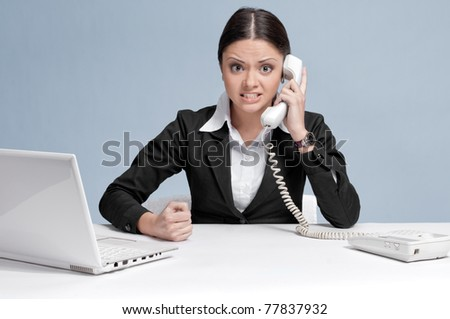 Casual angry business woman in office working with white table, laptop and talking by phone. Strict!