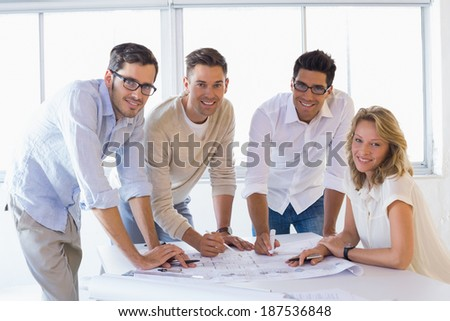 Casual architecture team working together smiling at camera in the office